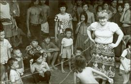 CUSO Mission, North-eastern Thailand - Unidentified woman walks between strings as crowd looks on