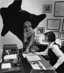Iona Campagnolo and assistant in office with black bear on wall