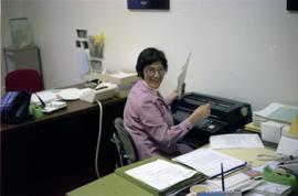 Woman at typewriter behind desk in an office