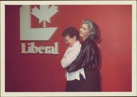 Iona Campagnolo hugs Rita Jauharne at 102 Bank St. in front of a Liberal sign in Ottawa, ON