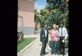 Iona Campagnolo standing between two unidentified men under a tree outside of a school at oversea...