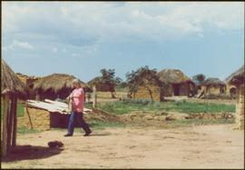 CUSO Mission in Angola - Iona Campagnolo walking on path between thatched-roof huts
