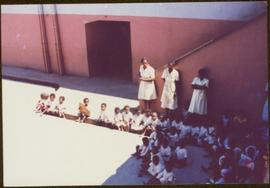 CUSO Mission in Angola - Three unidentified women stand over a group children seated in rows