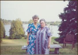 Iona Campagnolo and unidentified woman stand at stone bench overlooking a lake