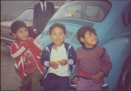 W.H.O. Trip, Ayacucho, Peru - Three unidentified children in front of a blue Volkswagen beetle