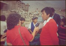 W.H.O. Trip, Ayacucho, Peru - Unidentified woman holding tape recorder to an unidentified man as children stand in background