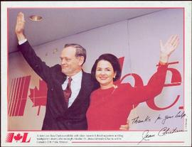 Commemorative photograph - Jean and Aline Chrétien waving in front of a red Liberal sign