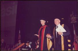 Honourary Doctor of Laws, Brock University - Iona Campagnolo grasping the hand of an unidentified man onstage, both in regalia