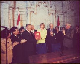 Ten unidentified men and women clap as a government minister presents the Nisga'a Final Agreement to a Nisga'a chief [?], 1999