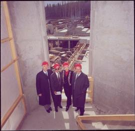Murray Sadler, John Backhouse, Iona Campagnolo, and Geoffrey R. Weller pose with hardhats in a stairwell during the construction of UNBC