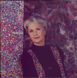 Portrait of Iona Campagnolo in black sweater and multicoloured vest, leaning against a paint-spla...
