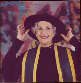 Portrait of Iona Campagnolo in regalia, smiling as she pulls on her Chancellor's hat