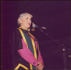 Iona Campagnolo speaking at a microphone in Chancellor's regalia