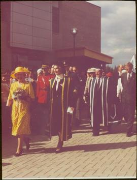 Queen Elizabeth II, Chancellor Iona Campagnolo, and President Geoffrey R. Weller walk through a crowd in front of the Geoffrey R. Weller Library, UNBC