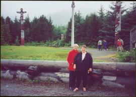 Iona Campagnolo and Margaret Anderson stand in front of totem poles