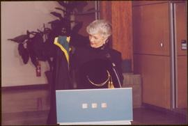 Chancellor's Farewell  - Iona Campagnolo holding chancellor's regalia from behind podium