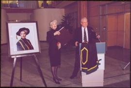 Chancellor's Farewell  - Iona Campagnolo standing with large book and roses, next to her portrait