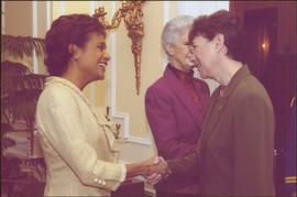 Governor General Michaëlle Jean shaking hands with an unidentified woman wearing a green suit, Lieutenant Governor Iona Campagnolo in background
