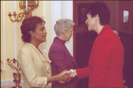 Governor General Michaëlle Jean shaking hands with an unidentified woman wearing a red suit, Lieutenant Governor Iona Campagnolo in background