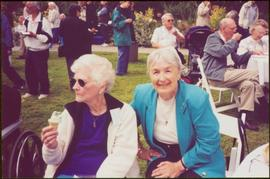 Two unidentified women sit together on crowded lawn at Government House in Victoria, BC