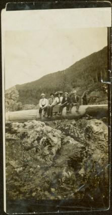 Sarah Glassey Sitting with Men on Log over Canyon