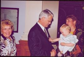Unidentified child reaches out from mother's arms to Gordon Campbell while another woman smiles i...