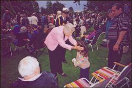 Iona Campagnolo, an aide-de-camp, and an unidentified child on crowded lawn at Government House, Victoria, BC