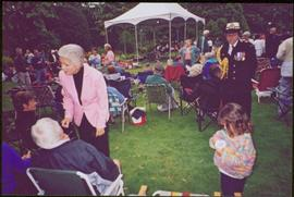 Iona Campagnolo, an aide-de-camp, and an unidentified child on crowded lawn at Government House, music tent in background