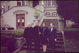 Close view of four unidentified women and Iona Campagnolo pose in front of steps