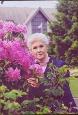 Portrait of Lieutenant Governor Iona Campagnolo standing beside a pink rhododendron with Government House in background, Victoria, BC