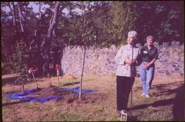 Iona Campagnolo holds shovel by an unidentified woman in front of newly planted tree