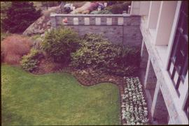 Carefully arranged gardens and lawn; three unidentified people work on garden in background behind wall