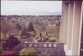 Distance view of three unidentified gardeners working behind Government House, with a view of Vic...