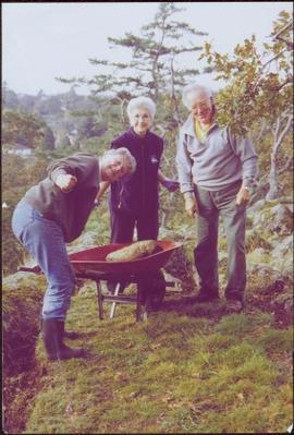 Iona Campagnolo moving rocks in Terrace Gardens with wheelbarrow and an unidentified woman and man