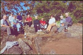 Nine gardeners and Iona Campagnolo sitting on rocky outcrop in Terrace Gardens, Government House,...