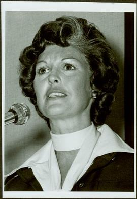 Close view of Iona Campagnolo speaking at a microphone, glancing up