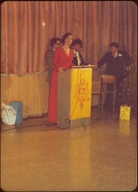 Iona Campagnolo, in formal wear, speaks into microphone at podium labeled '25'
