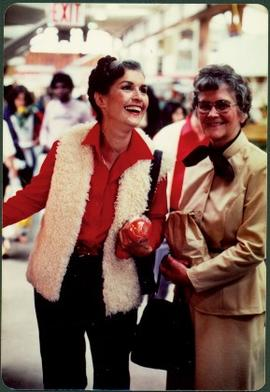 Iona Campagnolo holding tomatoes and laughing next to an unidentified woman holding a brown paper bag