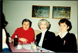 Iona Campagnolo sitting between two unidentified women at a restaurant