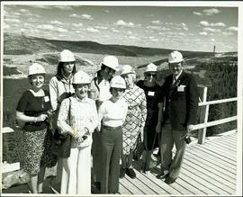 Group photo of unidentified women and men posing on a wooden platform overlooking James Bay, all ...