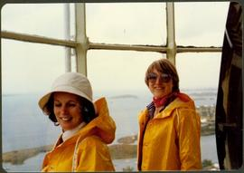 Two unidentified women in rain jackets at a window overlooking the ocean