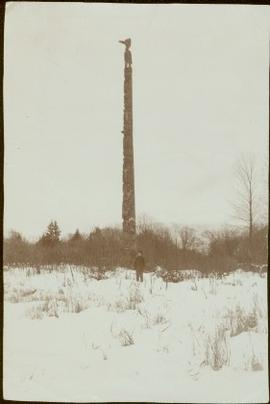 Young W.E. Collison standing by totem pole, Queen Charlotte Islands, BC