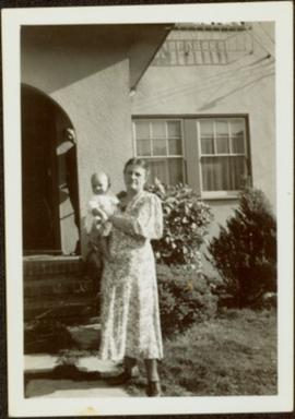 Woman Holding Infant in Front Yard