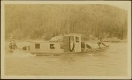 Crew of unidentified men poling a boat up Nass River, BC