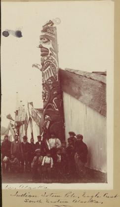 Group gathered at totem pole of eagle crest, Southeast Alaska