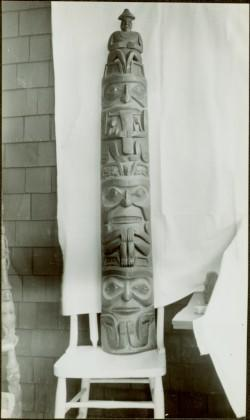 Model wooden totem pole on chair