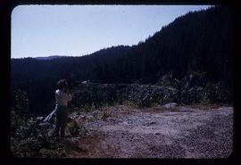 Unidentified woman photographing the Skeena Road in hillside