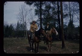 Two unidentified men riding horses on unknown ranch