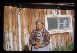 Unidentified woman standing in front of wood building