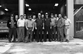 Group photo of thirteen men in front of fire trucks in Vancouver